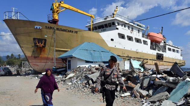 An Indonesian woman and policeman walk beside a stranded ship in Wani, Donggala on October 9, 2018, following the September 28 earthquake and tsunami that hit the area.(AFP Photo)