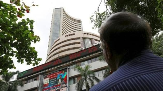 A man looks at a screen across a road displaying the Sensex on the facade of the Bombay Stock Exchange (BSE) building in Mumbai(REUTERS)