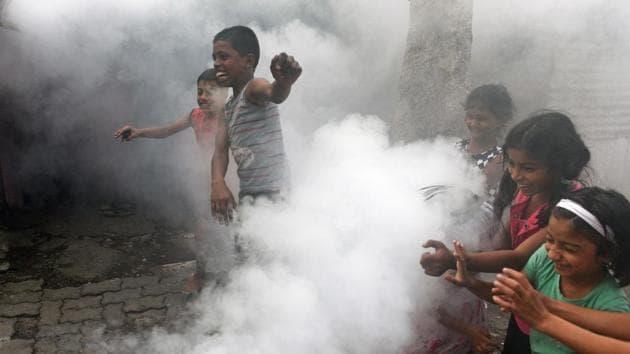 Children react during PMC worker fumigates in a slum area at Karve Nagar in Pune(Pratham Gokhale/HT Photo)
