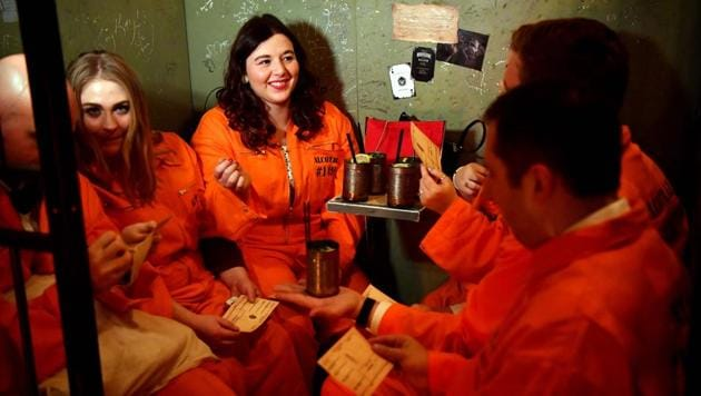 Guests sit in their cells at the Alcotraz Prison Cocktail Bar in east London.(AFP)