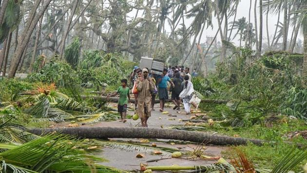 A group of people relocate to safer places as Cyclone Titli hits Barua village, in Srikakulam.(PTI Photo)
