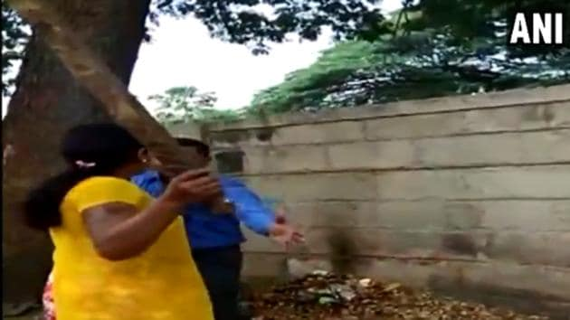 The video shows the woman dragging the man and beating him up with a stick.(ANI/Twitter)