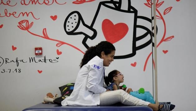 <p>Luana Vieira, who is two years old, and was born with microcephaly, reacts to stimulus during an evaluation session at the Altino Ventura rehabilitation...