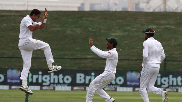 Pakistan batsman Mohammad Abbas (L) celebrates after dismissing Australian cricketer Travis Head during day four of the second Test match between Australia and Pakistan at Sheikh Zayed stadium in Abu Dhabi on October 19, 2018.(AFP)