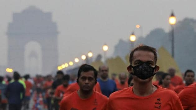 A runner wearing a face mask for protection from pollution takes part in the Airtel Delhi Half Marathon in New Delhi.(REUTERS)