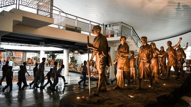 <p>Students from Kendriya Vidyalaya in Dwarka walk past a statue commemorating the Salt March of 1930, featuring Mahatma Gandhi and his followers, displayed...