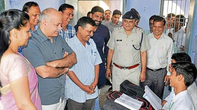 Delhi chief minister Arvind Kejriwal (centre) and his deputy Manish Sisodia (second from left) during a visit to a school at Bapoda village in Bhiwani district on Tuesday.(HT Photo)
