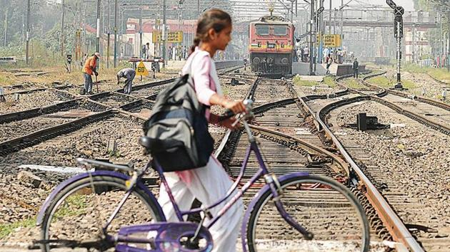 Barely a week after the Amritsar rail tragedy, a school girl is unmindful of the approaching train as she crosses the tracks in Jalandhar on Thursday.(HT Photo)