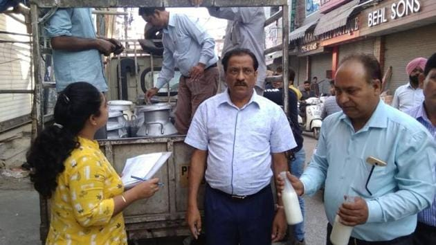 DHO Balwinder Singh (centre) seizing milk samples from a dairy in Jalandhar.(HT Photo)
