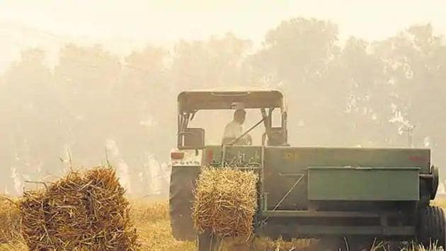 A baler is a machine used to compress crop residue into compact bales.(HT file)