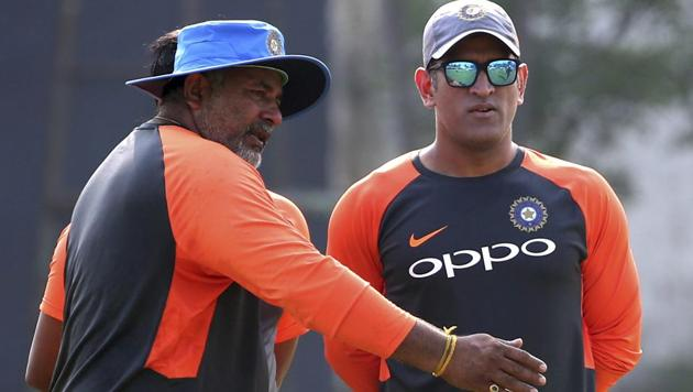 India's Mahendra Singh Dhoni, right, listens to bowling coach Bharat Arun during a practice session.(AP)