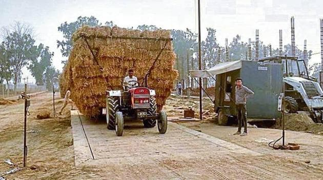 A farmer bringing bales of paddy straw for sale at the plant site on Bajakhana-Jaitu road.(HT Photo)
