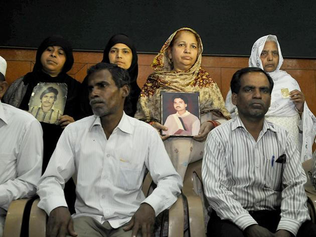 Relatives pose with photos of Hashimpura massacre victims in New Delhi.(HT file photo)