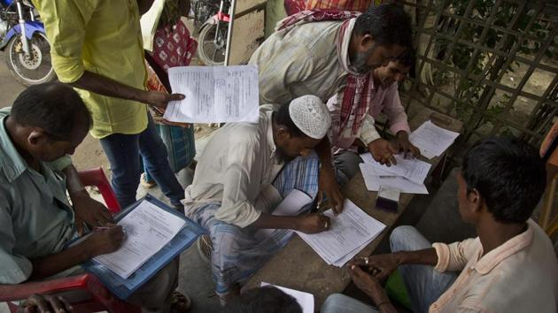 People whose names were left out in the National Register of Citizens (NRC) draft fill their forms to file appeals near a NRC center on the outskirts of Guwahati.(AP File Photo)