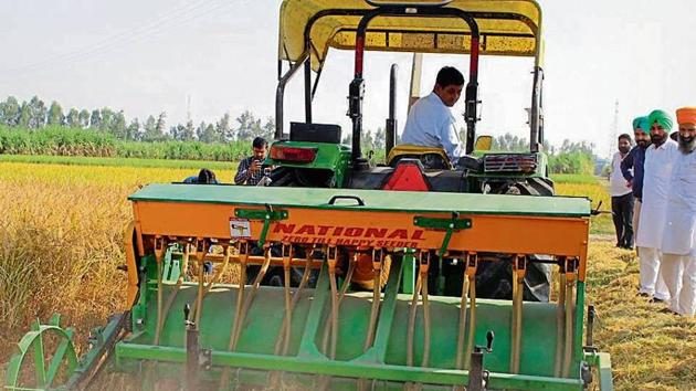 A farmer sows wheat using a mechanised seeder in a village in Karnal, Haryana.(HT Photo)