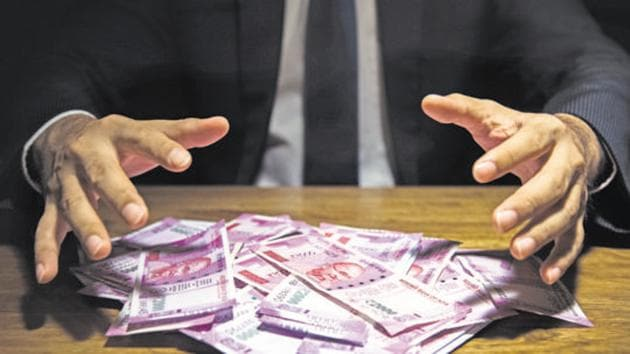 Businessman taking pile of money, Indian Rupee banknotes, on his desk in a dark office - corruption concept(Getty Images/iStockphoto)