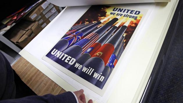 Brian Sylvester, director of the Rochester Public Library, examines original war posters at the library's archive in Rochester, New Hampshire.(AP)