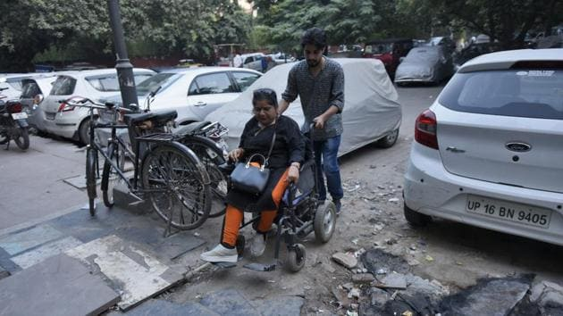 A differently- abled person commutes via her wheel chair, at Community Center Market, New Friends Colony, in New Delhi.(Burhaan Kinu/HT PHOTO)
