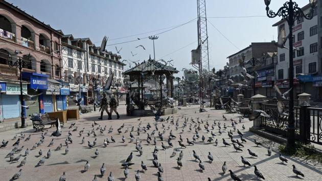 Indian paramilitary troopers patrol past pigeons during the first day of a strike called by Kashmiri separatists against attempts to revoke articles 35A and 370 of the state constitution, in Srinagar on August 30, 2018.(AFP)