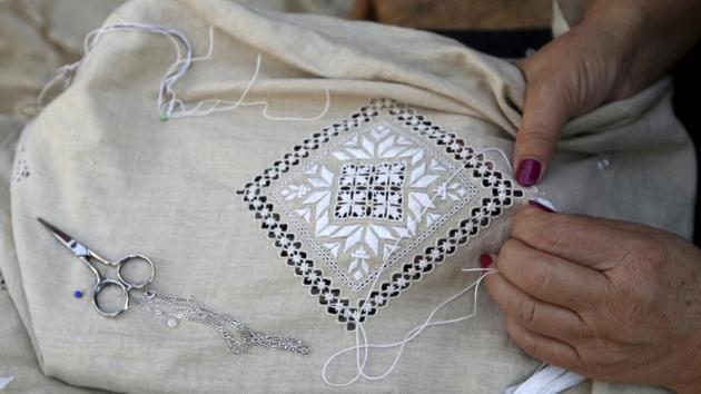 A woman stitches famous Lefkaritiko lace in Lefkara village, Cyprus.(AP Photo/Petros Karadjias)