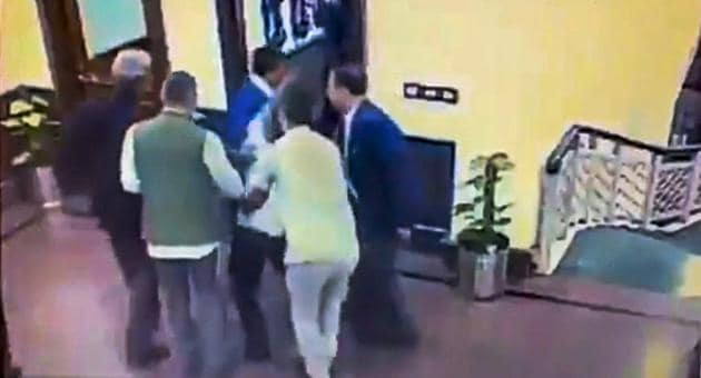 A still from a video posted by the AAP on its twitter account shows Anil Kumar being held after he allegedly threw chilli powder at Delhi chief minister Arvind Kejriwal, outside his chamber at Delhi Secretariat in New Delhi on November 20.(PTI Photo)