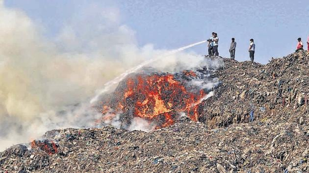 Locals, firefighters try to douse the fire at the Adharwadi dumping ground in Kalyan on Friday afternoon.(Rishikesh Choudhary/HT)