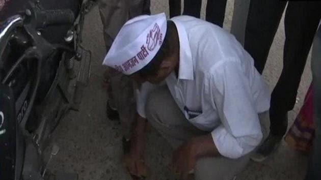 Sharad Singh Kumar, of Rashtriya Aamjan Party is polishing shoes of people to please voters(ANI)
