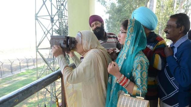 An Indian Sikh devotee looks through binocular towards the Gurdwara Kartarpur Sahib, which is situated in Pakistan, from Indian side at Dera Baba Nanak on the outskirts of Amritsar on November 25, 2018(AFP)