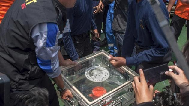 Members of the National Transportation Safety Committee lift a box containing the flight data recorder from a crashed Lion Air jet onboard a rescue ship anchored in the waters of Tanjung Karawang, Indonesia.(AP)