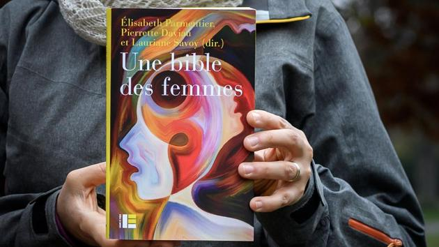 """Geneva theology professor Lauriane Savoy holds an edition of """"A Women's Bible.""""(AFP)"""