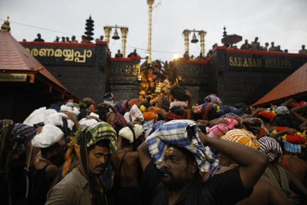 Devotees climb over the holy eighteen golden steps to worship diety of Hindu god Ayyapa at a temple premises in Sabarimala.(HT file photo)