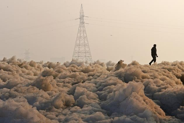 <p>A man walks along a large amount of toxic industrial waste-foam that has become a common sight along the banks of the heavily polluted Yamuna river in New...