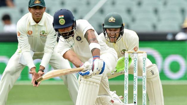 India vs Australia: India's captain Virat Kohli hits a ball as Australia's captain Tim Paine looks on during day three of the first Test.(AFP)