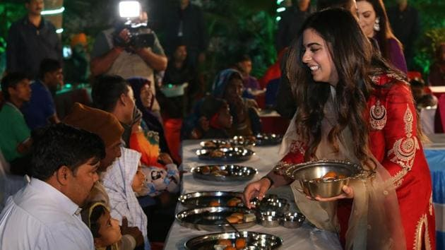 Isha Ambani (R), daughter of Reliance Industries chairman Mukesh Ambani, serving food to guests during an 'Anna Seva' ritual that coincides with pre-wedding functions ahead of her marriage with Anand Piramal.(AFP Photo)