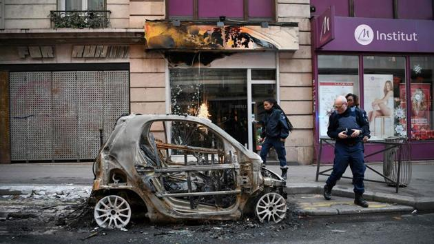 Police look at a burnt car in Beaubourg street in Paris, on December 9, 2018 a day after a 'yellow vest' protests as part of a fourth weekend of nationwide protests.(AFP Photo)