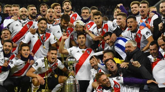 Players of River Plate celebrate with the trophy after winning the second leg match of the all-Argentine Copa Libertadores final against Boca Juniors, at the Santiago Bernabeu stadium in Madrid.(AFP)