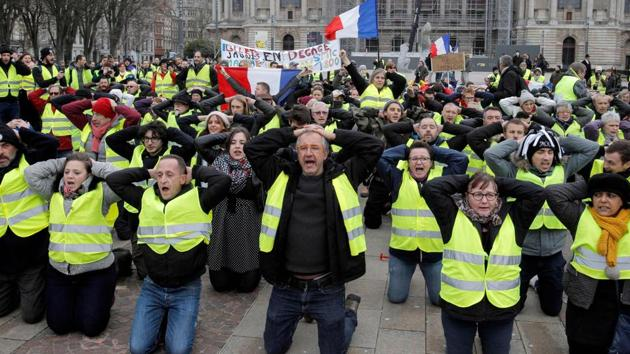 """Protestors wearing """"yellow vests"""" (gilets jaunes) demonstrate on their knees against rising costs of living in Lille, northern France, on December 8, 2018. The """"yellow vest"""" movement in France originally started as a protest about planned fuel hikes but has morphed into a mass protest against President's policies and top-down style of governing.(AFP)"""