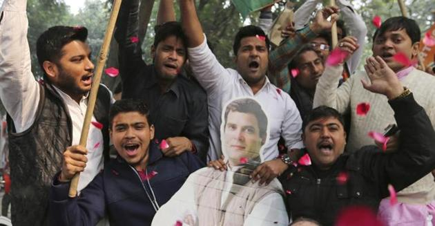 Assembly elections 2018: Congress party supporters hold a cut-out of party President Rahul Gandhi and celebrate outside the party headquarters in New Delhi.(AP)