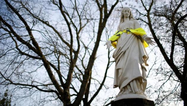 <p>A statue of the Virgin Mary wears a yellow hazard vest in a street in Nantes, France.</p> (Stephane Mahe / REUTERS)