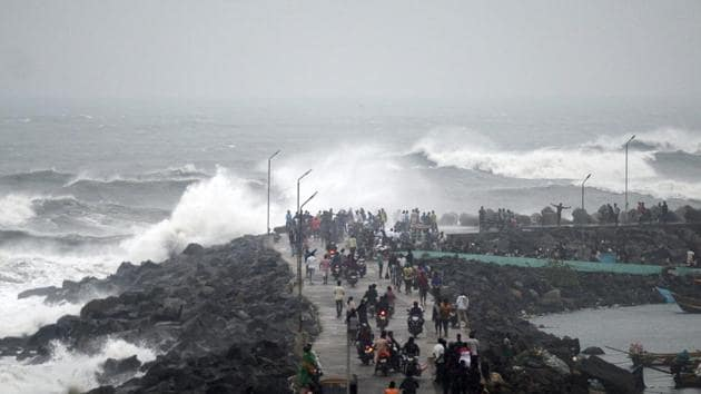 People walk along a breakwater at Kasimedu fishing harbour as Cyclone Phethai approaches Chennai on Sunday.(AFP Photo)