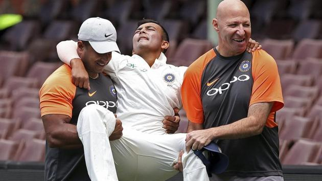 Sydney: India's Prithvi Shaw, center, is carried by support staff after rolling his ankle while attempting a catch during their tour cricket match against Cricket Australia XI in Sydney.(AP)