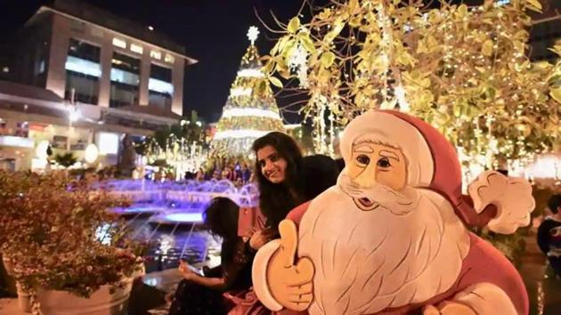 People take photographs infront of a Christmas tree at a mall in New Delhi.(Burhaan Kinu / Hindustan Times)