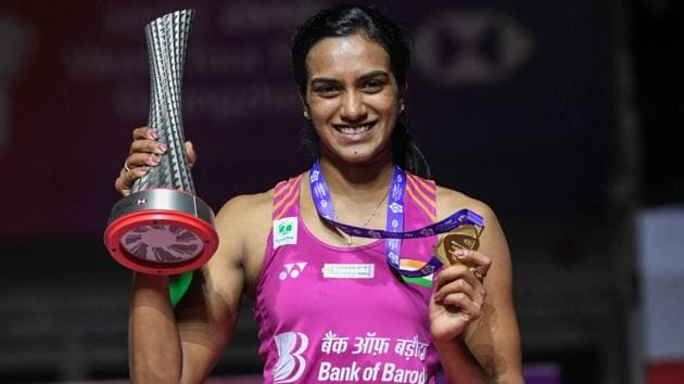 PV Sindhu poses with the trophy after the women's singles final match at the 2018 BWF World Tour Finals badminton competition.(AFP)