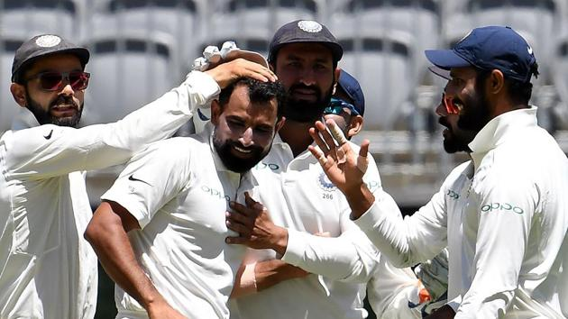 India's captain Virat Kohli (L) greets paceman Mohammed Shami (C) for his fifth wicket during day four of the second Test cricket match between Australia and India in Perth.(AFP)