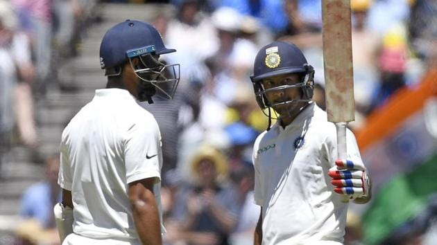 India's Mayank Agarwal, right celebrates with team mate, left Cheteshwar Pujara after scoring a half century on day one of the third cricket test between India and Australia in Melbourne.(AP)