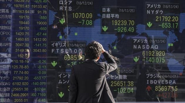 A man looks at an electronic stock board outside a securities firm in Tokyo, Japan. Japan's Nikkei 225 index, which plunged 5 percent on Tuesday, picked up 0.5 percent to 19,241.87.(Bloomberg)