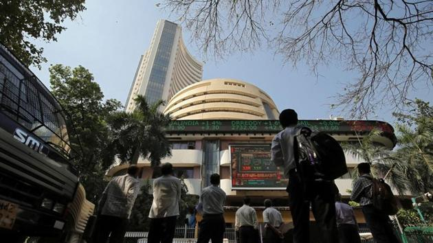 People look at a screen displaying the Sensex results on the facade of the Bombay Stock Exchange (BSE) building in Mumbai.(REUTERS)