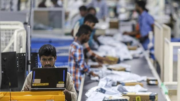 An employee uses a laptop computer while packages move along a conveyor belt at the Amazon.com Inc. fulfillment center in Hyderabad.(Bloomberg)
