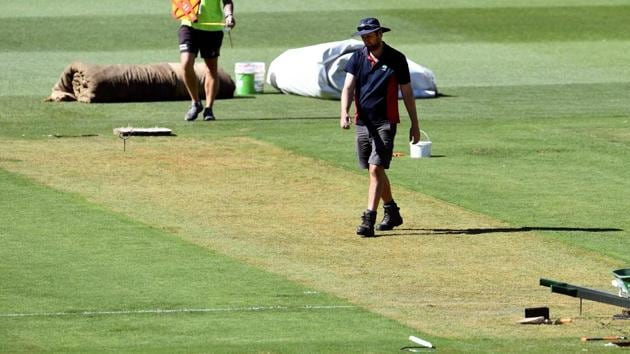 Melbourne Cricket Ground (MCG) curator Matt Page walks over the wicket ahead of the third Test between India and Australia.(AFP)