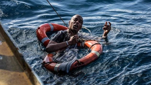 A migrant is being rescued on January 4, 2019 with buoys and a rope, after he dived in the cold Mediterranean off Malta's coast from the Dutch-flagged Sea-Watch 3 rescue vessel, in a attempt to reach the shore by swimming.(AFP)